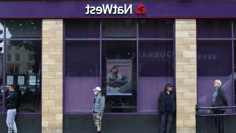 a group of people walking in front of a store: NatWest Group is the new name for the former RBS group of banking brands