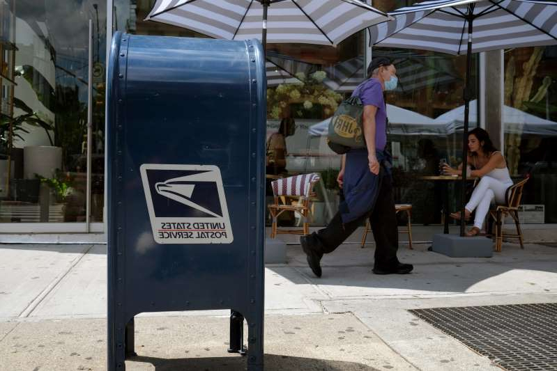 a person standing on a sidewalk: On any given day, the Postal Service delivers more than 425 million pieces of mail.