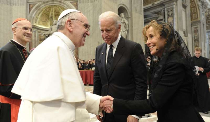 Valerie Biden Owens, Joe Biden, Tarcisio Bertone standing next to a person in a suit and tie: Former vice president Joe Biden and his sister Valerie Biden Owens are greeted by Pope Francis in Saint Peter's Basilica, 2013.