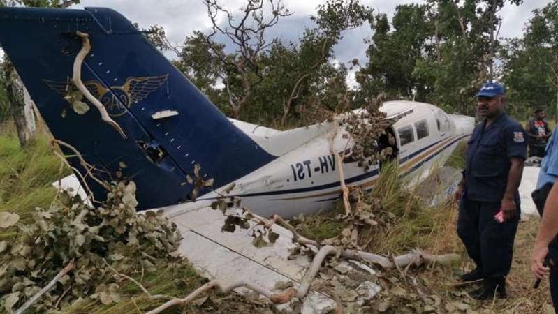 a person standing next to an airplane: The alleged drug operation was exposed when a light plane carrying 500 kilograms of cocaine crashed in PNG in July. (Supplied: Russell Saigomi)