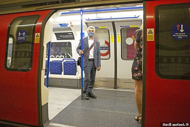 a person standing on a subway train: Sadiq Khan boards a TFL tube train at Leicester Square Tube station while wearing a mask