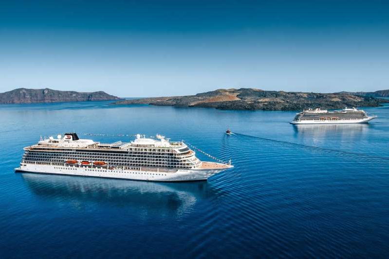 a small boat in a body of water: Courtesy of Viking Cruises The Viking Sea and Viking Star cruise ships in Santorini