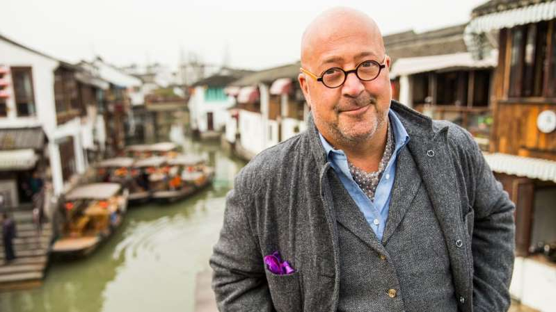 Andrew Zimmern standing in front of a building: Travel Channel