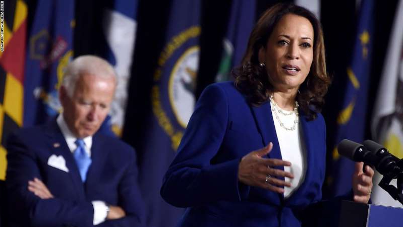 Kamala Harris wearing a suit and tie: Democratic presidential nominee and former US Vice President Joe Biden listen to his vice presidential running mate, US Senator Kamala Harris, speak during their first press conference together in Wilmington, Delaware, on August 12, 2020. (Photo by Olivier DOULIERY / AFP) (Photo by OLIVIER DOULIERY/AFP via Getty Images)