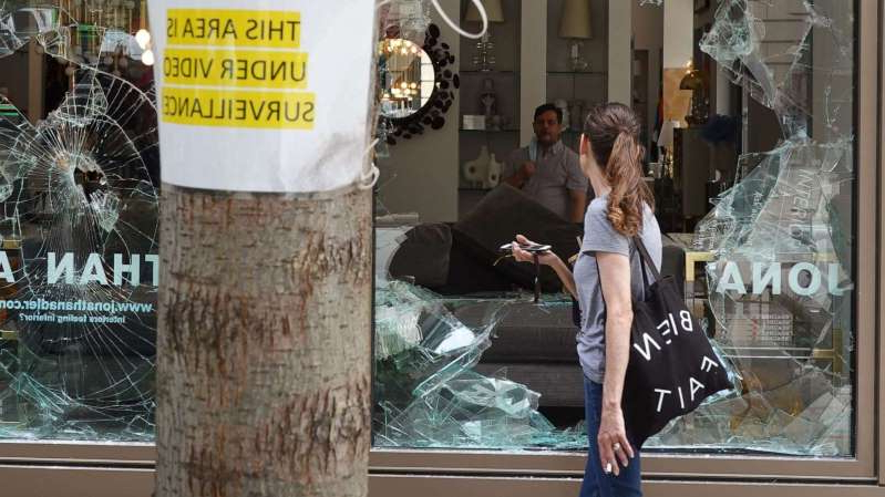 a person standing in front of a store: A woman looks through the shattered glass window of an interior design store that was looted on Aug. 10, 2020, in Chicago.