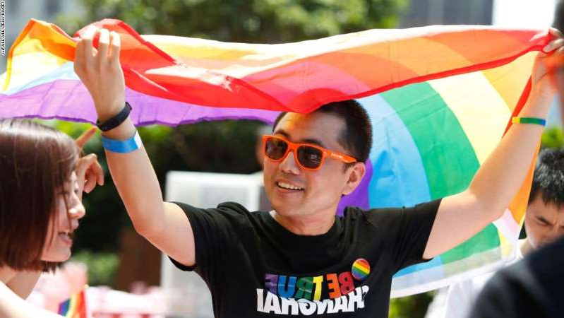 a young man holding a colorful kite: A participant holds a rainbow flag after taking part in a Pride event in Shanghai on June 17, 2017.