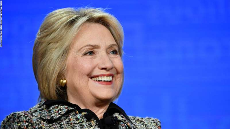 Hillary Clinton wearing glasses and smiling at the camera: Hillary Clinton of