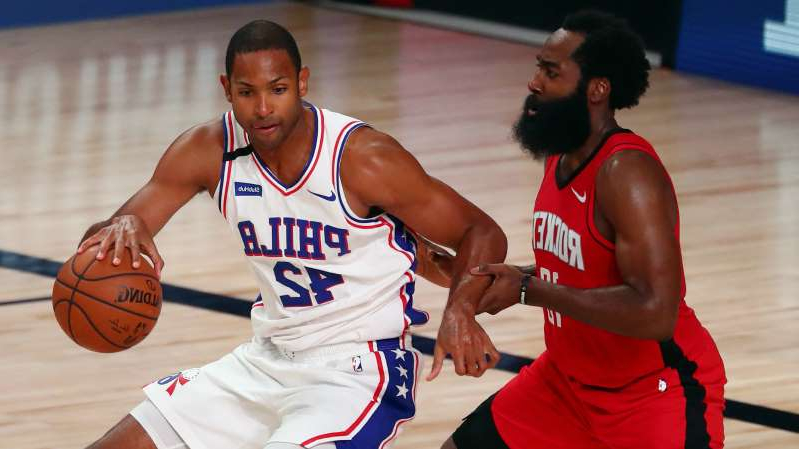 a baseball player holding a basketball: Houston Rockets star James Harden (L) and the Philadelphia 76ers' Al Horford (R)