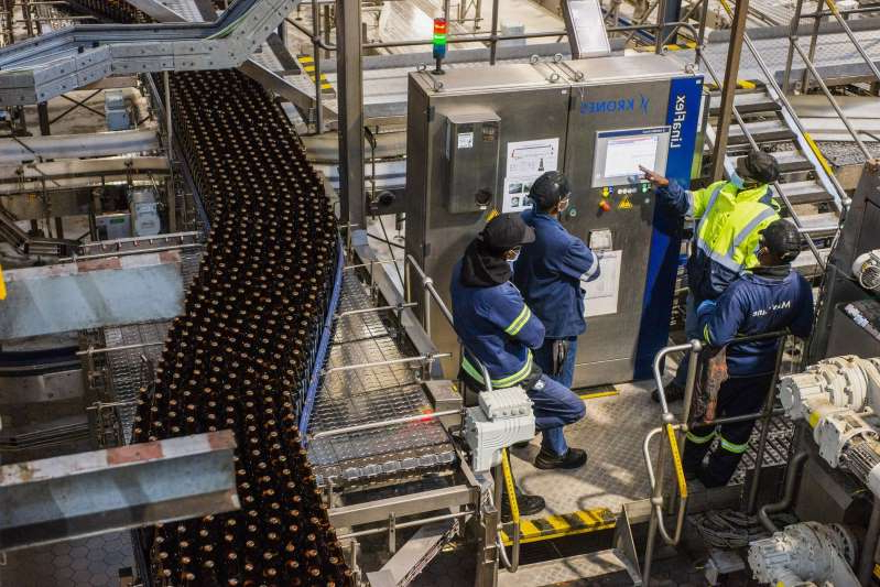 Workers stand and speak by the bottling line control unit at the SABMiller Plc Alrode brewery and bottling plant, a unit of Anheuser-Busch InBev SA, in Johannesburg, South Africa, on Tuesday, Aug. 11, 2020. South Africa's ban on alcohol sales has put investment projects worth at least 12.8 billion rand (2 million) on hold.