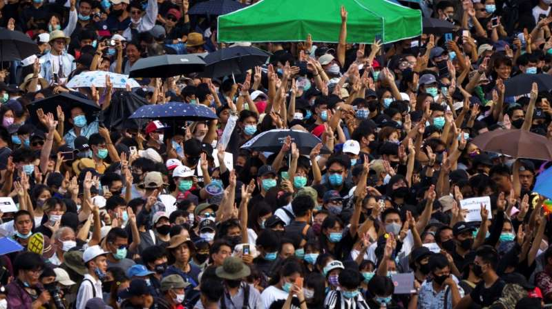a group of people standing in front of a crowd: Protesters gathered at Bangkok's Democracy Monument for one of the biggest demonstrations since Prayuth took power in a 2014 coup. [Reuters]