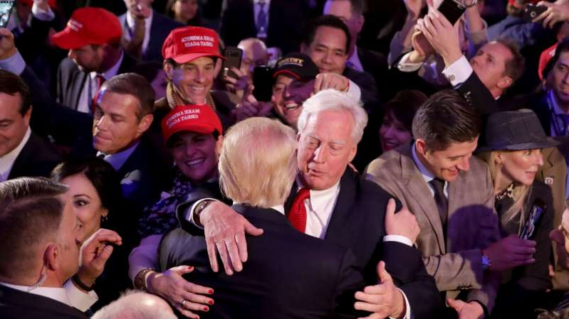 a group of people standing in front of a crowd: Robert Trump, pictured here hugging his brother Donald in the early morning hours of November 9, 2016 after Donald Trump delivered his acceptance speech, has died.