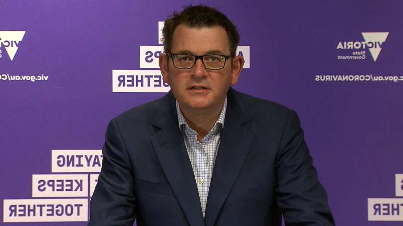 Daniel Andrews holding a sign posing for the camera: Victoria Premier Daniel Andrews has urged people in regional areas to be tested for coronavirus.