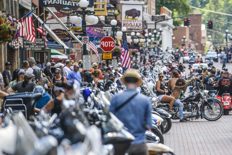 a person riding a motorcycle down a street next to a crowd of people: Motorcyclists ride through downtown Deadwood, South Dakota during the 80th Annual Sturgis Motorcycle Rally on August 8, 2020.