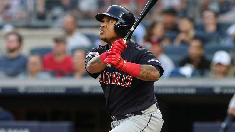 a baseball player holding a bat: Aug 16, 2019; Bronx, NY, USA; Cleveland Indians third baseman Jose Ramirez (11) watches his solo home run in the second inning against the New York Yankees at Yankee Stadium.