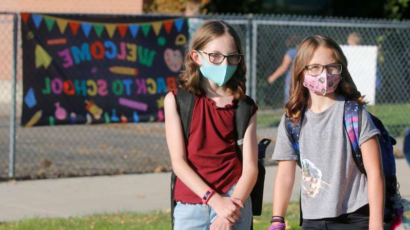 a little girl walking on a sidewalk: Cimmie Hunter, left, and Cadence Ludlow arrive for the first day of school on Monday at Liberty Elementary School in Murray, Utah.