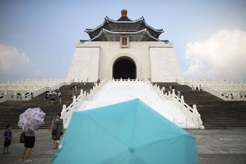 a group of people standing in front of Chiang Kai-shek Memorial Hall: Tourists with umbrellas walk in front of the Chiang Kai Shek Memorial Hall in Taipei, Taiwan, on Wednesday, July 24, 2013.