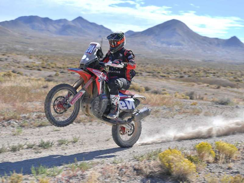 a man riding a motorcycle down a dirt road: With precious few opportunities to race in this COVID-shuttered world, the Monster Energy Honda Team gave Ricky Brabec the opportunity to chase one of his goals: soloing and winning Vegas-to-Reno. After starting near the back of the Open Pro field, he methodically marched to the front to win, though the team's engineers saw it more as the first day of durability testing that'll be more like torture testing for the next four weeks straight in desert temperatures exceeding 110 degrees much of each day.