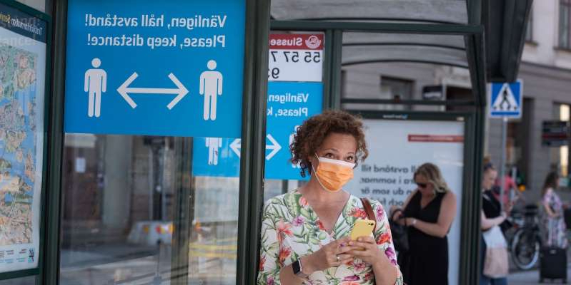 a person standing in front of a store: A woman wears a face mask as she waits at a bus stop on June 26, 2020 in Stockholm, Sweden. Stina St Jernkvist/TT News Agency/AFP via Getty Images
