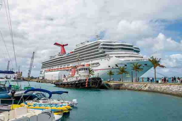 a boat is docked next to a body of water: Carnival Sunrise docked in Bermuda. (Photo by Gene Sloan/The Points Guy)