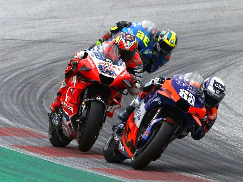 a man riding a motorcycle on a track: Miguel Oliveira overtook Jack Miller and Pol Espargaró as the two went wide on the final corner, giving himself and Tech3 KTM a first-ever MotoGP win.