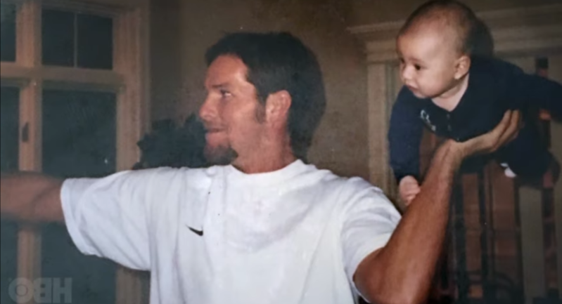 a man standing in a room: Brett Favre with baby Clay Johnston.