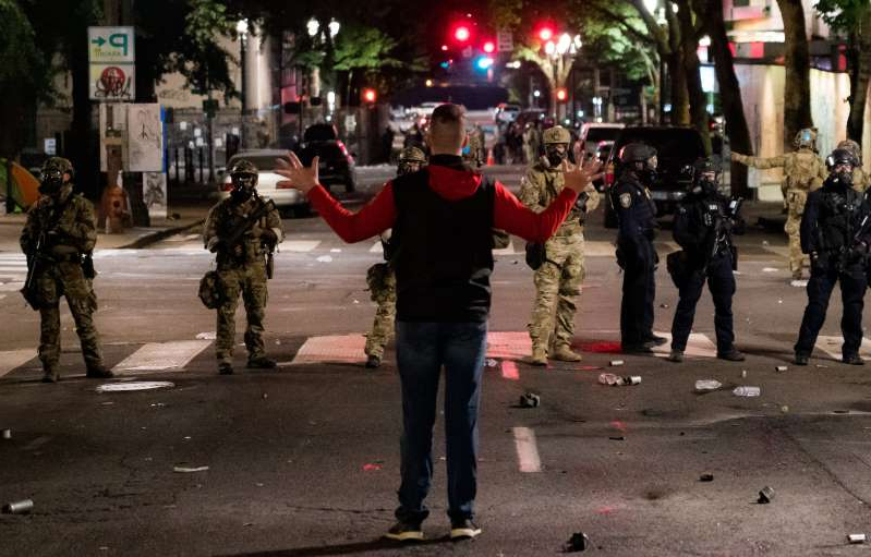 a group of people walking down the street: A lone man confronts a line of federal agents during protests near the federal courthouse in Portland, Oregon, in the early hours of July 24, 2020. They fired a teargas canister at his feet moments later.