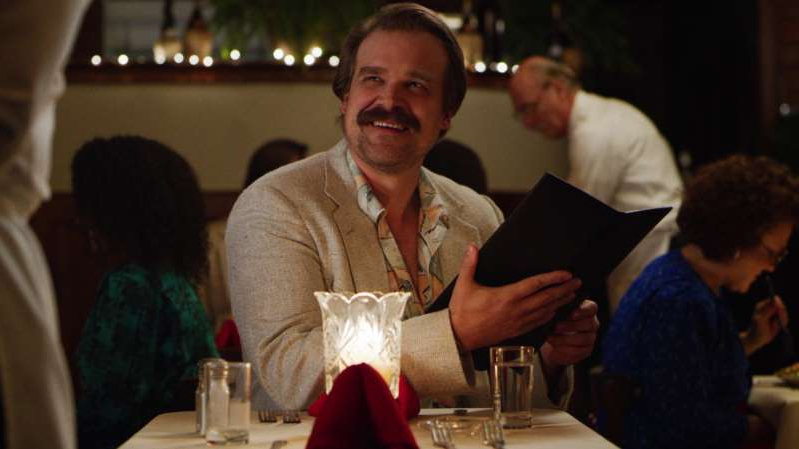 David Harbour sitting at a table: David Harbour's Hopper in Stranger Things season 4