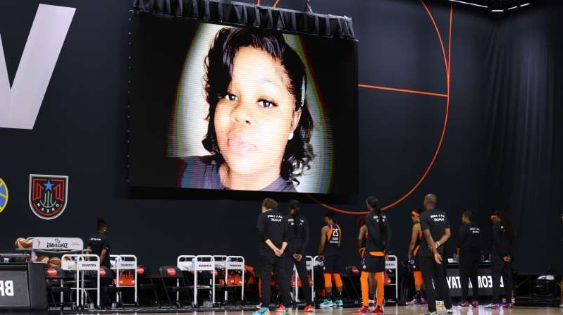 a person standing in front of a television: The Connecticut Sun honour Breonna Taylor prior to a game against the Minnesota Lynx in August 2020 at Feld Entertainment Center in Palmetto, Florida [Stephen Gosling/NBAE/Getty Images via AFP]