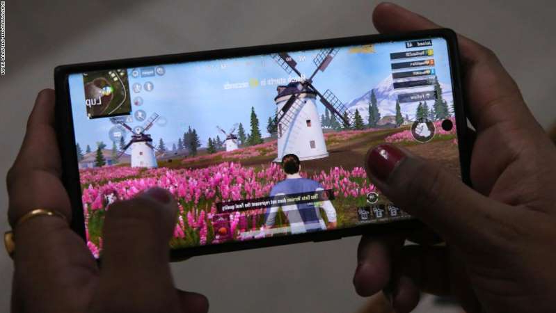 a hand holding a video game: Mandatory Credit: Photo by RAJAT GUPTA/EPA-EFE/Shutterstock (10763559d) A woman plays PlayerUnknown's Battlegrounds (PUBG) online game on her mobile phone in New Delhi, India, 02 September 2020. India's National government has announced it is banning additional 118 Chinese phone applications. Chinese mobile app ban in India, New Delhi - 02 Sep 2020