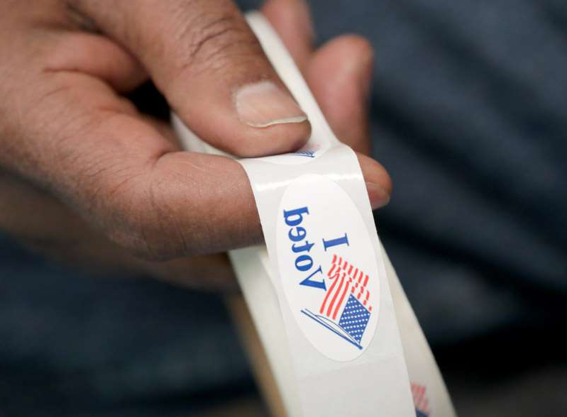 a close up of a hand: Poll worker Charles Hawkins holds