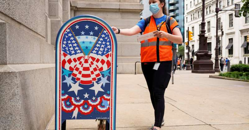 a person walking down a sidewalk in front of a building: A woman wearing a mask to prevent the spread of coronavirus disease (COVID-19) casts her ballot in the primary election in Philadelphia, Pennsylvania, June 2, 2020.