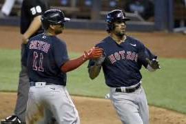 a baseball player holding a bat on a field: Boston Red Sox's Rafael Devers, right, and Xander Bogaerts celebrate after scoring during the sixth inning of a baseball game against the Miami Marlins, Thursday, Sept. 17, 2020, in Miami. (AP Photo/Gaston De Cardenas)