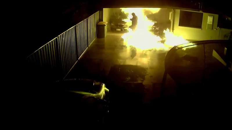 a blurry image in a dark room: One of the men who snuck onto the premises had to run through the flames to escape. (Supplied: ACT Policing)