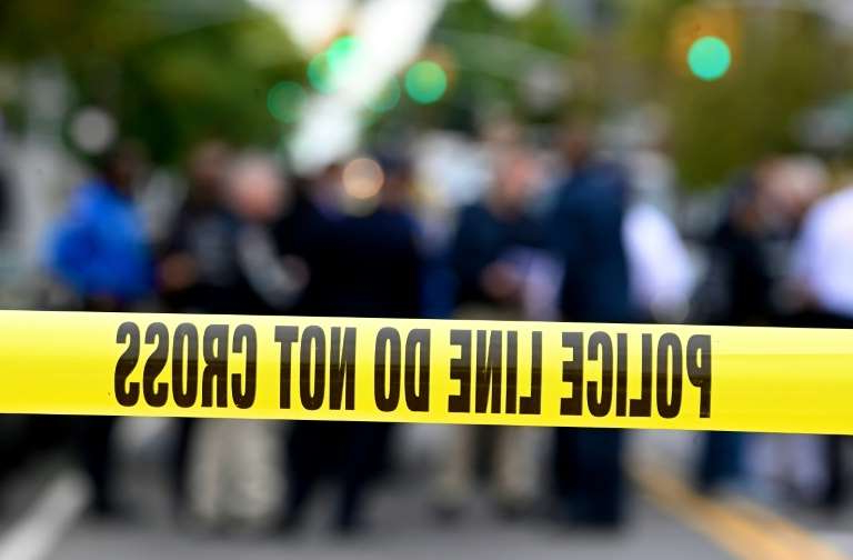 a close up of a street: Police tape secures a crime scene outside a club after a shooting in Brooklyn on October 12, 2019. At least four people died and three were wounded in a shooting at a social club in New York eary Saturday, police said. No one has been arrested over the shooting, which took place in Brooklyn, and the motive and exact circumstances are not known, a New York police official told AFP. The local affiliate of ABC News described the place where the shooting took place as an after-hours club.