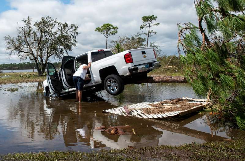 a group of people on a boat in the water: A man checks on his truck as it rests on a tree in Perdido Key, Fla., on Thursday, Sept. 17, 2020. Hurricane Sally made landfall as a Category 2 early Wednesday morning.