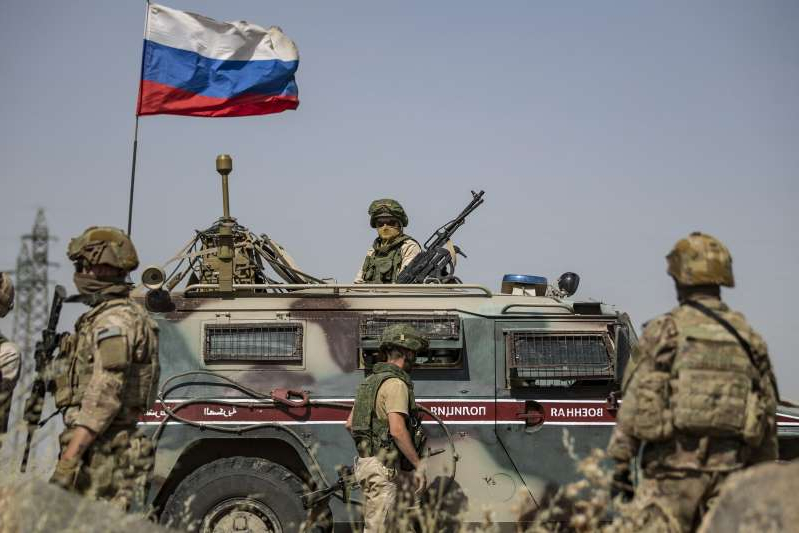 a group of people standing in front of a military vehicle: U.S. soldiers stand near a Russian military vehicle in the northeastern Syrian town of Al-Malikiyah at the border with Turkey, on June 3. Amid a series of confrontations between the two forces, the Pentagon told Newsweek:
