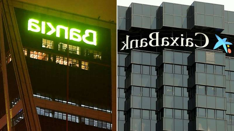 a large clock mounted to the side of a building: Caixabank and Bankia are Spain's third and fourth largest lenders respectively