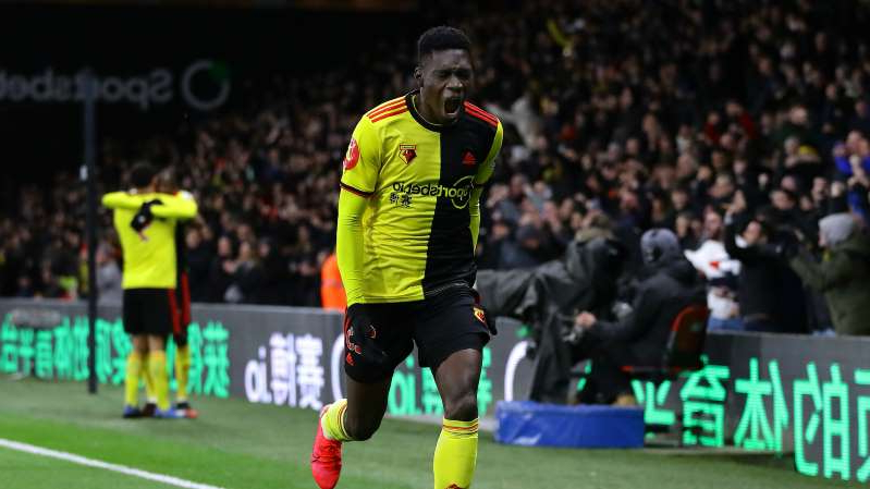 a man holding a football ball in front of a crowd: Ismaila Sarr celebrates scoring for Watford