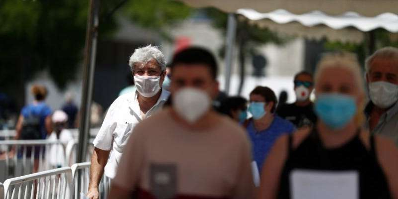 a man standing in front of a crowd: People waiting to be tested for the coronavirus in Spain. Reuters