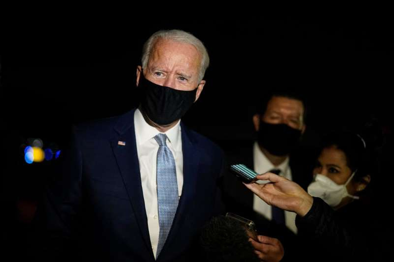 a man wearing a suit and tie talking on a cell phone: Joe Biden speaks to reporters at Wilkes-Barre Scranton International Airport after participating in a CNN town hall event on September 17, 2020 in Avoca, Pennsylvania.