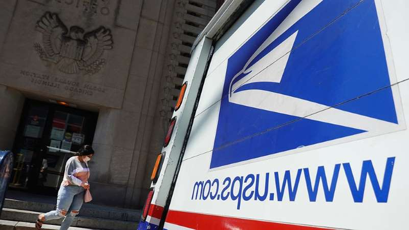 a person standing in front of a building: Judge issues nationwide injunction against Postal Service changes