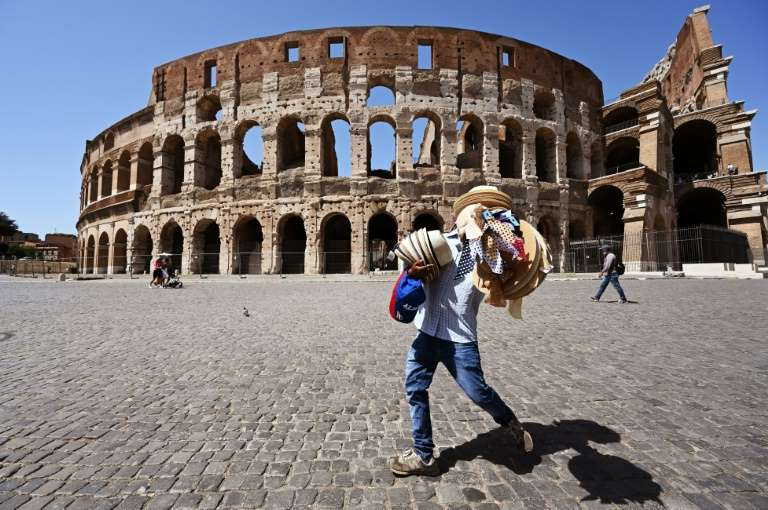 a group of people walking in front of a building: The coronavirus has killed more than 35,000 people in Italy