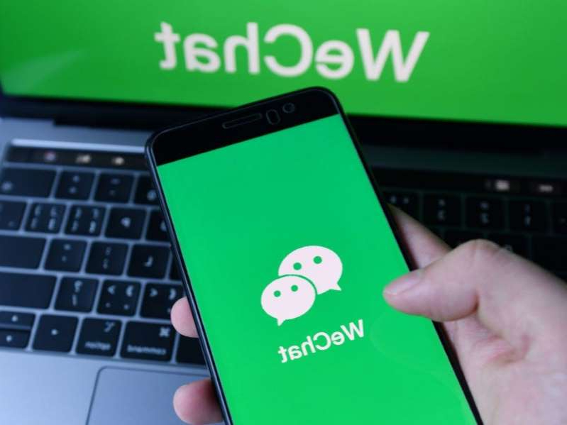 a hand holding up a laptop computer: President Trump's new executive order threatens Chinese app WeChat.