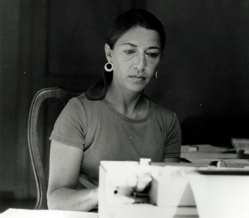 a man sitting at a table in front of a laptop: Ruth Bader Ginsburg types while on a Rockefeller Foundation fellowship in Italy in 1977.
