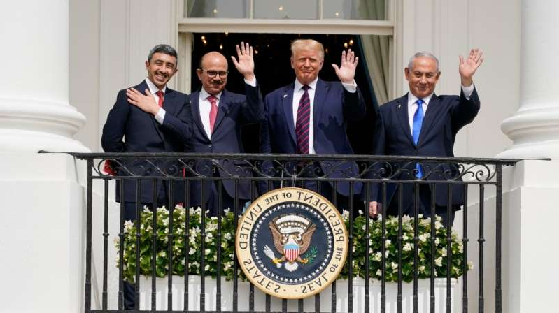 a man standing in front of Benjamin Netanyahu, Donald Trump, Abdullatif bin Rashid Al Zayani, Abdullah bin Zayed Al Nahyan posing for the camera: From left, Israeli Prime Minister Benjamin Netanyahu, President Donald Trump, Bahrain Foreign Minister Khalid bin Ahmed Al Khalifa and United Arab Emirates Foreign Minister Abdullah bin Zayed Al Nahyan at the White House, September 15, 2020, in Washington [AP Photo/Alex Brandon]