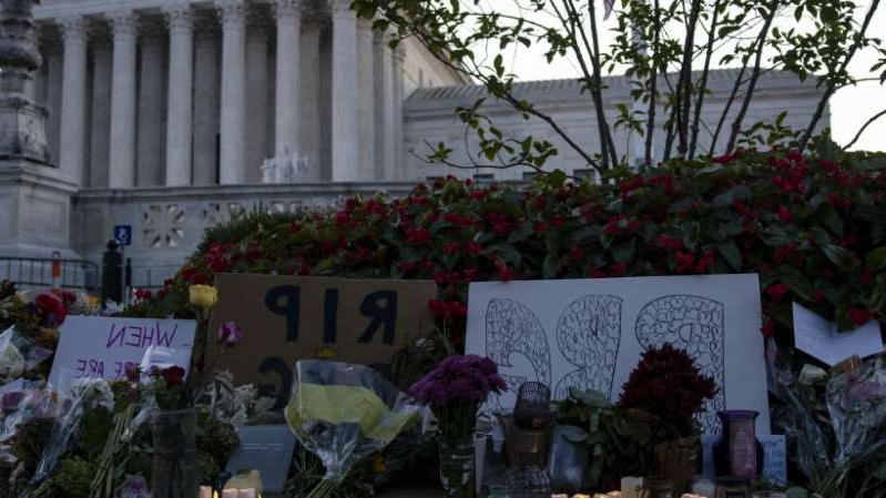 a sign on the side of a building: Memorial forms outside Supreme Court to honor Ginsburg