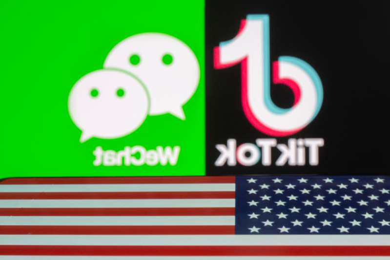 A U.S. flag is seen on a smartphone in front of displayed Tik Tok and WeChat logos in this illustration taken September 18, 2020. REUTERS/Dado Ruvic/Illustration