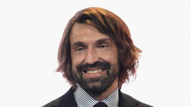 Andrea Pirlo wearing a suit and tie smiling at the camera: Juventus legend Andrea Pirlo