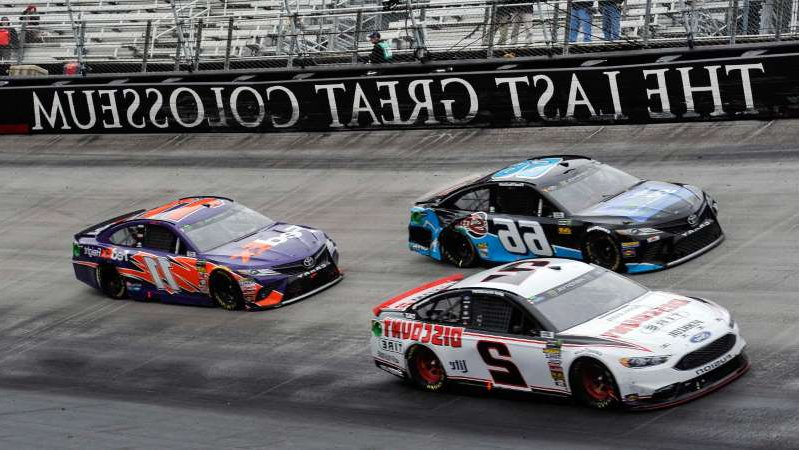 a car parked in a parking lot: NASCAR Cup Series driver Martin Truex Jr. brings out a caution after hitting the wall during the Coca-Cola 600 at Charlotte Motor Speedway.