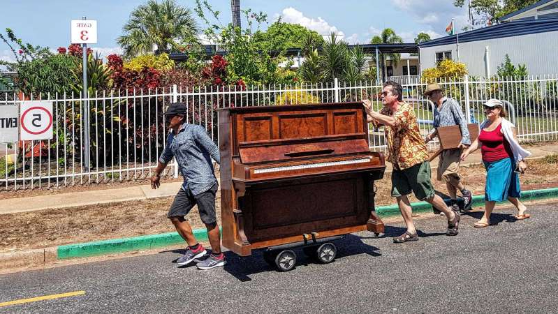 a group of people posing for a picture: Walking Simon Niblock's son's 'new' 1910 German-made Lipp and Sohn piano to its new home. (Supplied: Natalia Laska)
